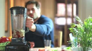 Young man blending fruits in blender, in slow motion, graded