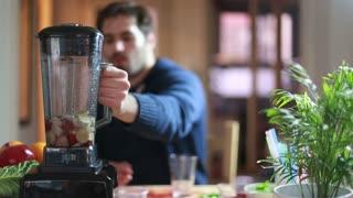 Young man blending fruits in blender, in slow motion