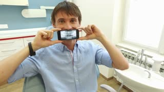 Young man holding smartphone with photo of dental X-ray and looking at camera