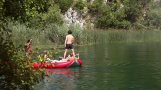 Young man jumping off canoe into water and having fun with a friends on the Mreznica river, graded, in slow motion
