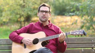 Young man playing acoustic guitar and singing while sitting on park bench, graded