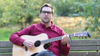 Young man playing acoustic guitar and singing while sitting on park bench