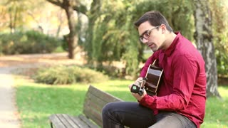 Young man playing the guitar and singing in the park, graded