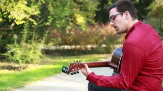 Young man playing the guitar and singing in the park