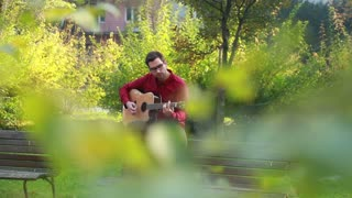 Young man playing the guitar and singing while sitting on a park bench