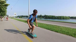 Young man riding on a longboard with friends in background