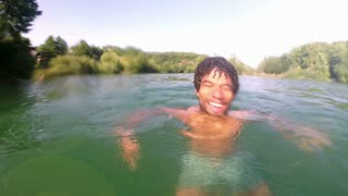 Young man smiling and shaking water off his head in river