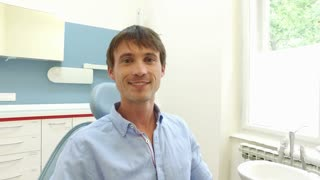 Young man with healthy white teeth smiling and looking at camera at dentist