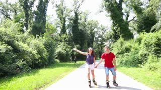 Young woman and man rollerblading and performing in park on a beautiful warm day and man jumping.