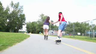 Young woman and man rollerblading and performing in park on a beautiful warm day, doing tricks