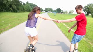 Young woman and man rollerblading and performing in park on a beautiful warm day, holding hands.