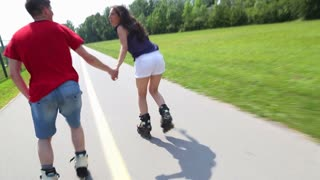 Young woman and man rollerblading on a beautiful sunny summer day in park, holding hands