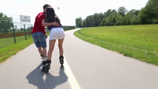 Young woman and man rollerblading on a beautiful sunny summer day in park, holding waist