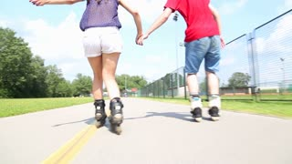 Young woman and man rollerblading on a beautiful sunny summer day in park, view of legs