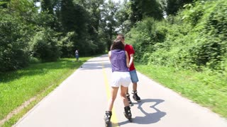 Young woman and man rollerblading on a sunny day in park, holding hands.