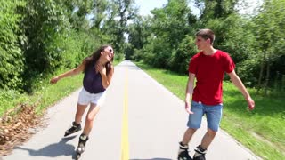 Young woman and man rollerblading on a sunny day in park