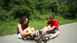 Young woman and man sitting at the road, putting their rollerblades on their feet.