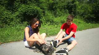 Young woman and man sitting on track, putting their rollerblades on their feet.