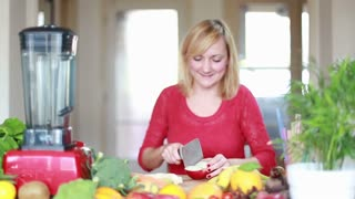 Young woman chopping apple for fruit shake