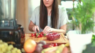 Young woman cutting strawberries for fruit smoothie, graded