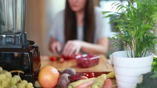 Young woman cutting strawberries for fruit smoothie