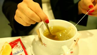 Young woman�۪s hand mixing hot tea in restaurant