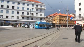 ZAGREB, CROATIA - AUGUST 21: People walk along city street with old houses and travel by tramway in Zagreb, Croatia on August 21, 2012. Zagreb Tram run by the Zagrebacki elektricni tramvaj (ZET).
