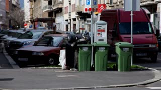ZAGREB, CROATIA - JUNE 21: Person looking for empty bottles in trash for recycling in Zagreb, Croatia on June 21, 2012. The crisis has brought many people to find ways to earn extra income.