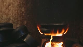 Zoom out of burning fire heating a pot for cooking in local kitchen in Sri Lanka