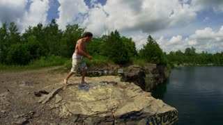 A young man does a back flip off of a tall cliff into water