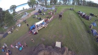 Aerial of motocross rider jumping big ramp