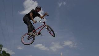 BMX rider doing bar spin on a dirt jump