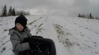 Boy pulling sled up hill in snow - slow motion