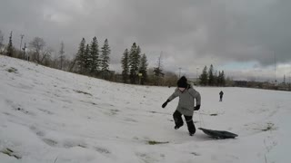 boy running up hill with sled