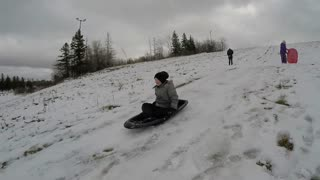 Brother And Sister Boy Tobogganing On Snow Sled Hill