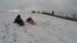 Brother And Sister Racing In Sleds Down Snowy Hill