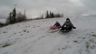 Brother And Sister Sled Racing On Snow Hill