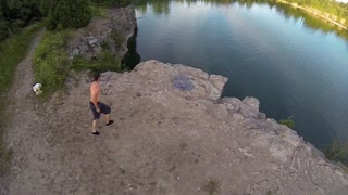 Extreme Sport Cliff Jumping into water - Young man back flip