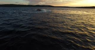 Jet Ski ride off into the sun set on lake