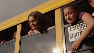 Kids hanging out the school bus window