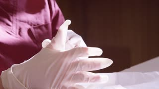 Nurse slowly putting on rubber gloves