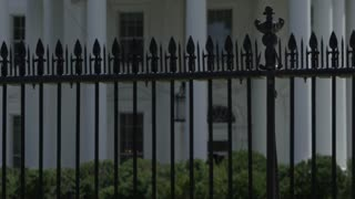 Rack focus from fence to white house in washington dc