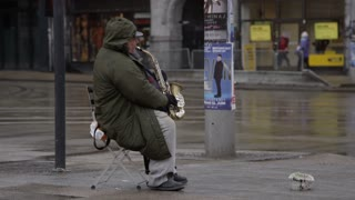 Street performer playing saxophone on a wet downtown street