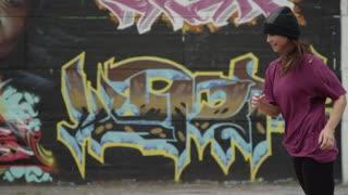 Talented Female Break Dancer Performing in front of Graffiti Wall