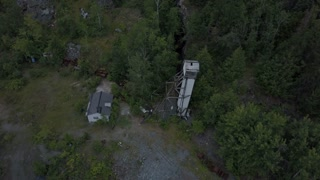 Aerial of abandoned mining site and head frame falling apart
