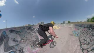 BMX back flip on summer day bicycle stunts in a skateboard park in urban setting