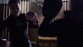 Female athlete punching and kicking in slow motion dojo