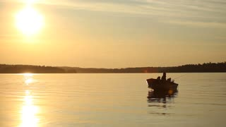 Wide Shot Of Man In A Fishing Boat At Sunset On Fresh Water Lake
