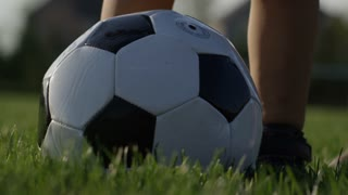 Zoom out from soccer ball showing dad teaching son