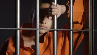 Young woman locked up behind bars - Minorities in prison